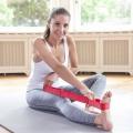 Eine Frau zeigt Übung mit der Übungsschlaufe, sitzend