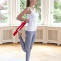 Eine Frau zeigt wie die Übungs-Schlaufe für gezielte Engpassdehnungen z.B. in den Beinen eingesetzt werden kann.