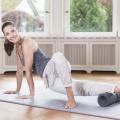 Eine Frau führt am Boden eine Übung für die Aussenseite des Beines aus. Sie rollt dabei mit dem Eigengewicht seitlich liegend, über die grosse Faszienrolle.