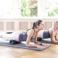 Zwei Frauen rollen sich mit ihrem eigenen Körpergewicht, liegend über die grosse Faszienrolle. Zu Beginn liegt die Rolle unter dem Rist, dann wird langsam nach oben, zur Körpermitte gerollt. Die beiden Frauen stützen sich dabei mit den Unterarmen auf der Matte ab.