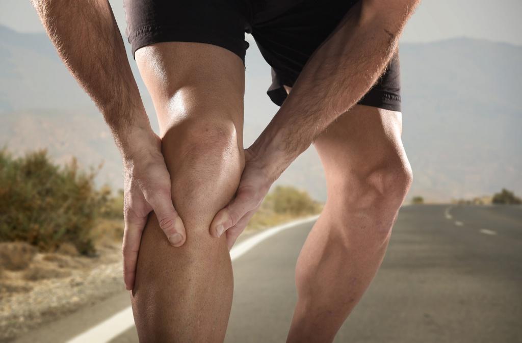Ein Sportler langt sich an sein Knie, welches nach Überanstrengung schmerzt.