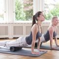 Zwei Frauen rollen mit ihrem Eigengewicht der Oberschenkel über die grosse FaYo-Faszienrolle.