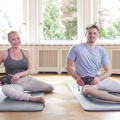 Ein Mann und eine Frau sitzen auf Yogamatten und massieren sich mit der Faszien-Kugelrolle die Oberschenkel.